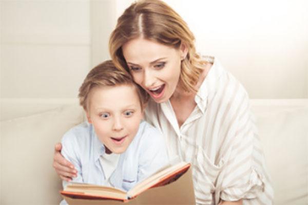 Мама с сыном увлечено читают книгу