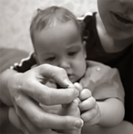 Мама рассматривает пальчик маленького ребенка
