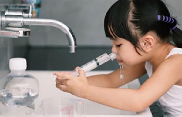 Девочка промывает нос над раковиной