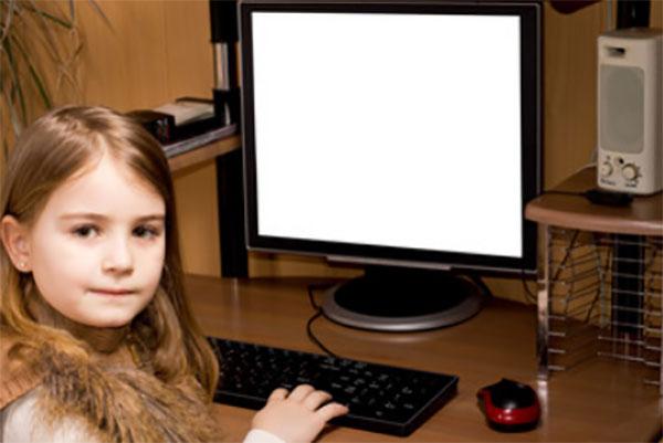 Девочка сидит возле персонального компьютера