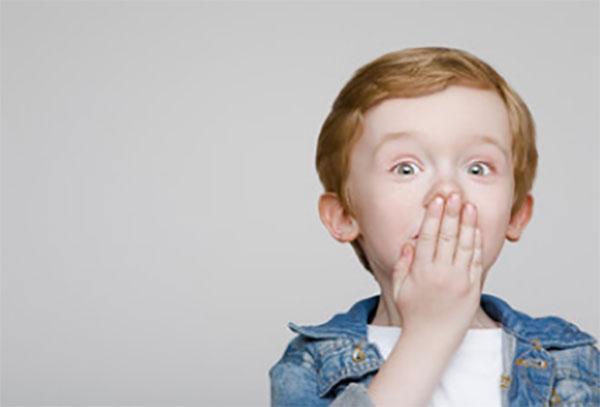 Мальчик прикрывает рукой свой нос и рот