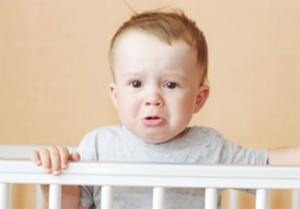 Грустный малыш стоит внутри кроватки возле перил
