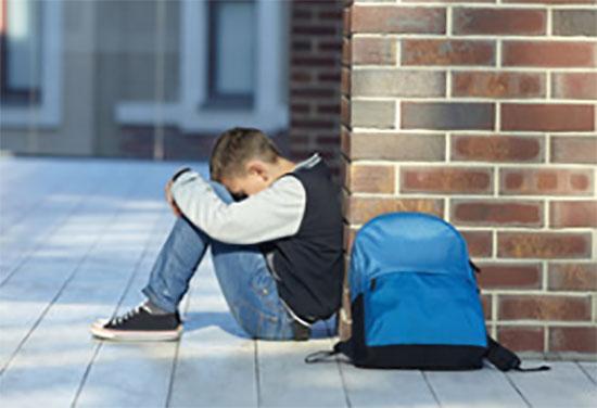 Мальчик сидит возле стены, рядом лежит рюкзак