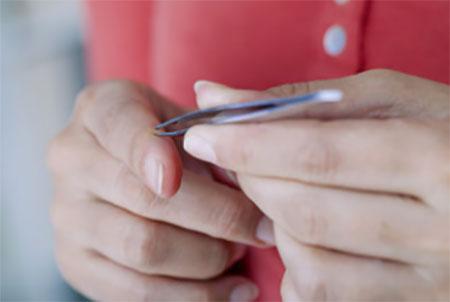 Женщина держит в руках пинцет