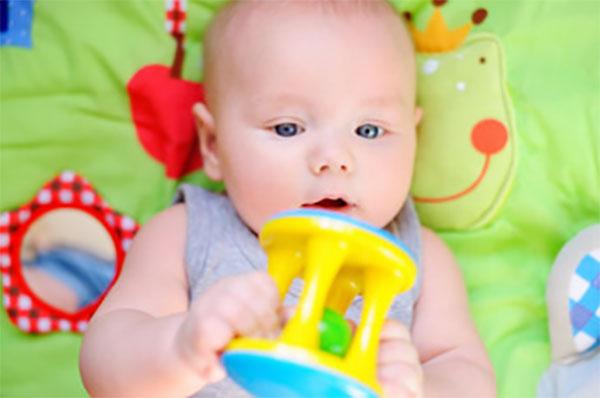 Грудничок внимательно смотрит на игрушку, которую держит в руке