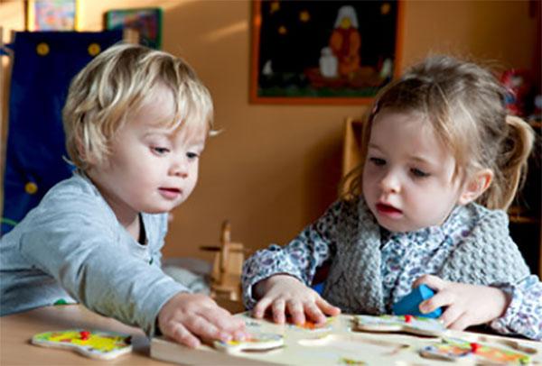 Два ребенка сидят за столом, вместе играют развивающей игрой