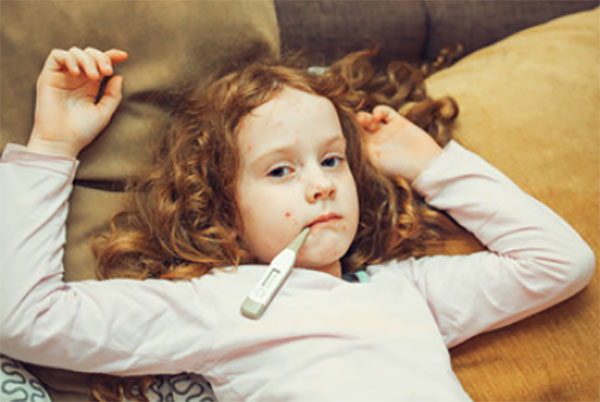 Девочка с градусником во рту, на теле есть сыпь