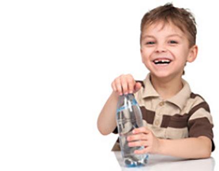 Мальчик откручивает крышку бутылки