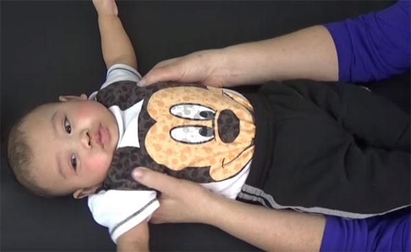 Грудной ребенок, которому вытягивают тело