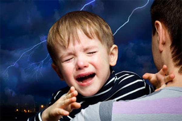 Мальчик на руках у родителя. За окном сверкает молния