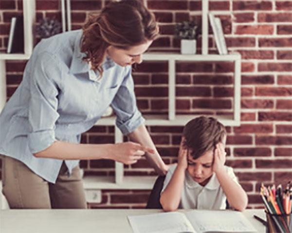 Мальчик сидит за столом над тетрадкой, а мама его ругает