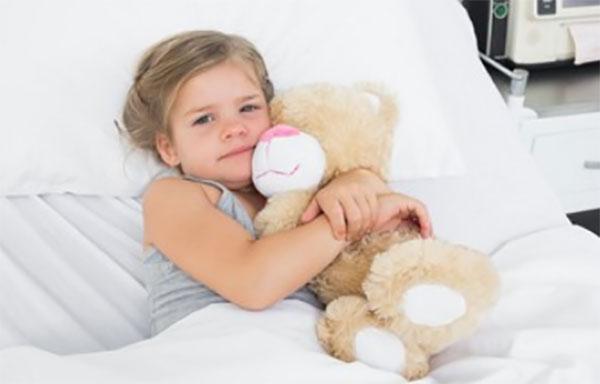 Девочка лежит в постели и обнимает плюшевого медведя