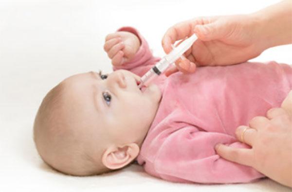 Ребенку дают лекарство со шприца