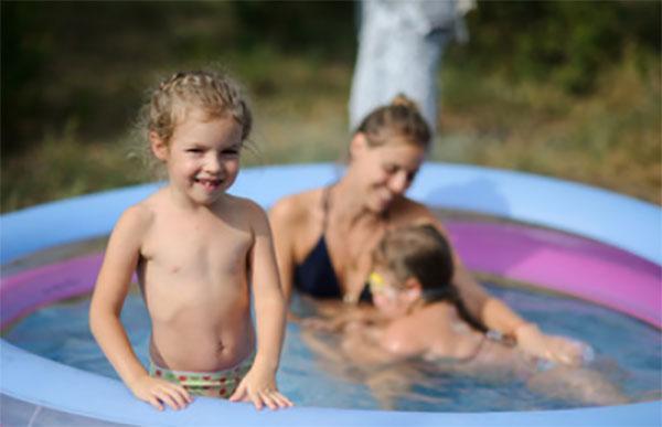 Мама с двумя детьми в уличном бассейне