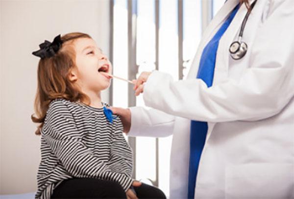Доктор осматривает ротовую полость ребенка