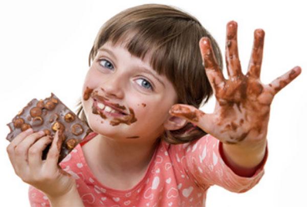 Девочка ест шоколад с орехами