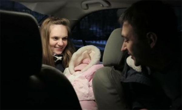 В салоне автомобиля мама с новорожденным, завернутым в конверт и водитель