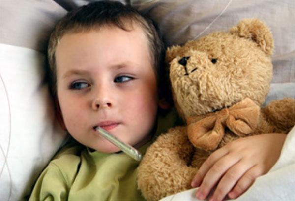 Мальчик лежит в постели с градусником во рту