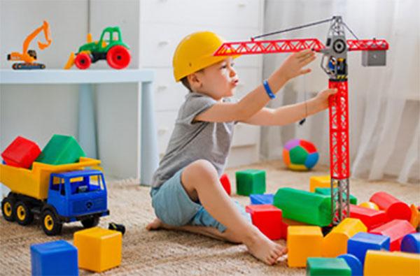 Мальчик играет на полу, рядом кубики и строительный кран