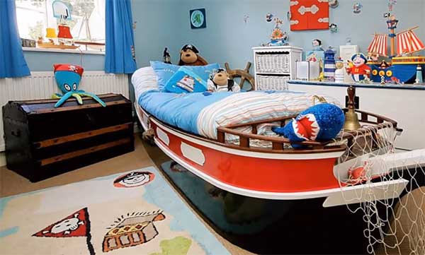 Кровать в виде корабля, на комоде корабль, на полу стоит сундук, на нем осьминог