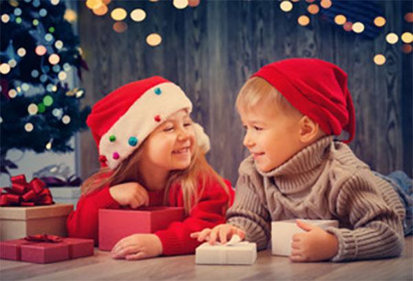 Девочка и мальчик лежат на полу в новогодних шапках