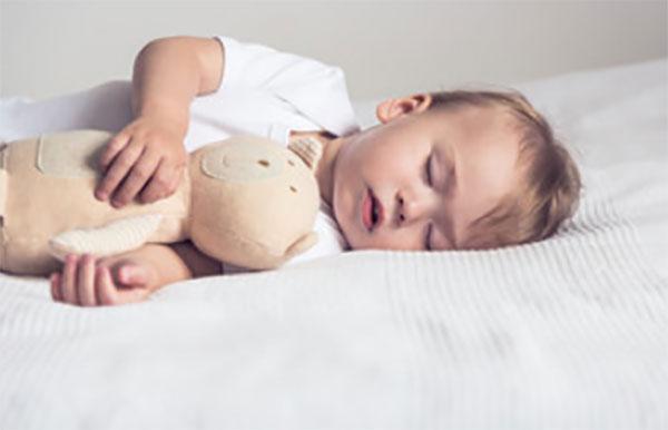 Ребенок спит на кровати