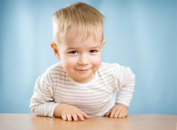 Двухлетний мальчик облокотился на стол