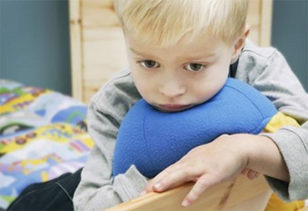 Печальный ребенок сидит возле спинки кровати