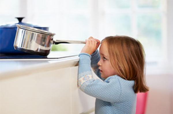 Девочка тянет ковшик с кипятком с плиты прямо на себя