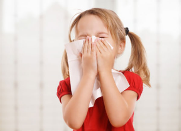 Девочка собирается чихнуть, прикладывает платок к носу
