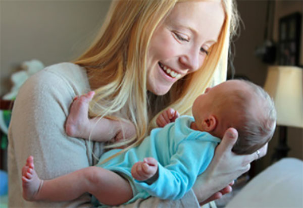 Мама держит грудничка на руках и улыбается