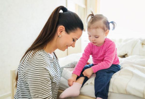 Девочка сама надевает носки. Мама смотрит на это и улыбается