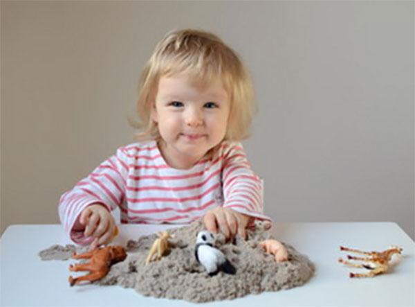 Девочка по песку разложила игрушечных животных