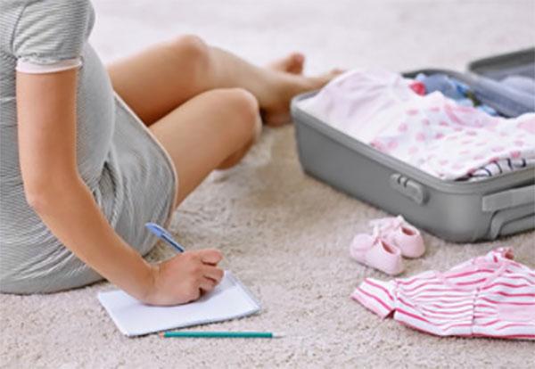Беременная девушка собирает вещи в роддом