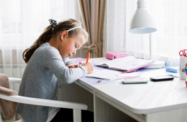 Девочка за столом пишет уроки