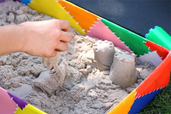 Кинетический песок лежит в декорированной песочнице