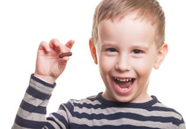 Мальчик держит в руке капсулу и улыбается