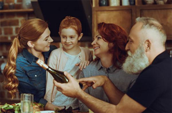 Семья сидит за столом, у дедушки бутылка в руках
