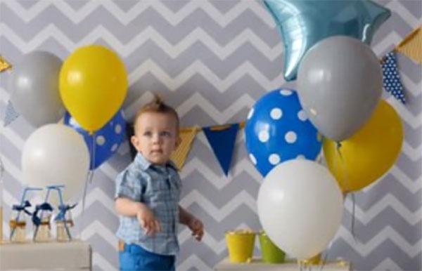 Мальчик. Рядом много надувных шаров различной окраски