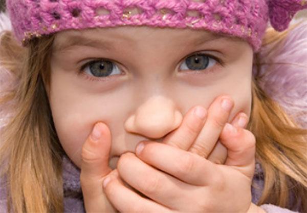 Девочка прикрывает руками рот