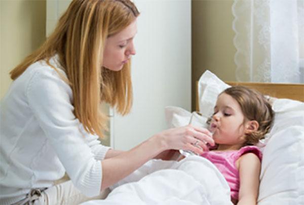 Мама дает девочке, лежащей в постели, лекарство