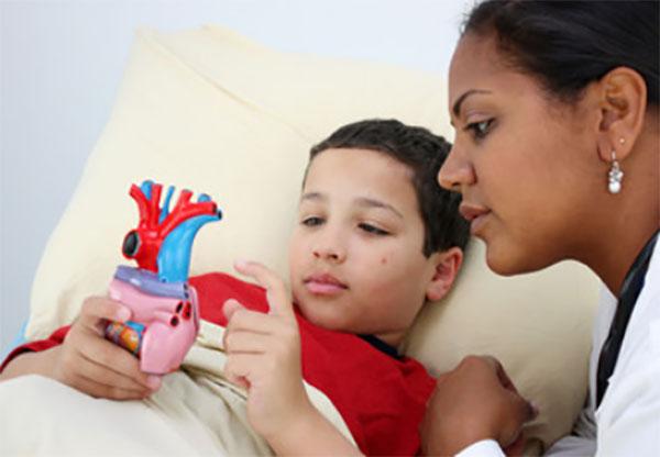 Ребенок лежит в постели и держит модель сердца, рядом доктор