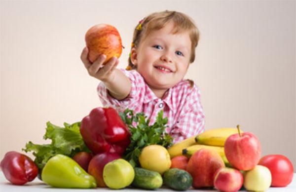 Ребенок с разложенными на столе фруктами и овощами