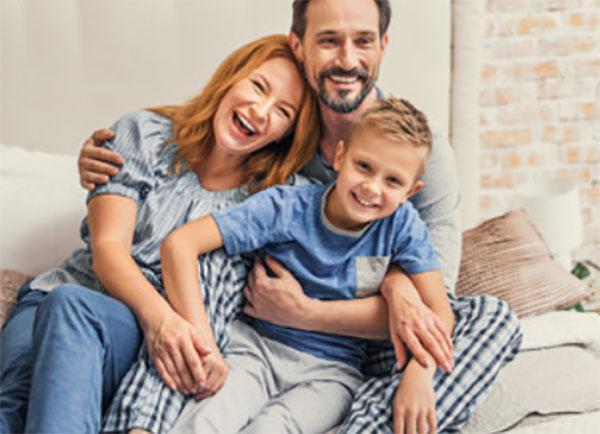 Папа, мама и сын обнимают друг друга, сидя на диване