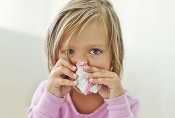 Девочка с насморком, держит платочек у носа