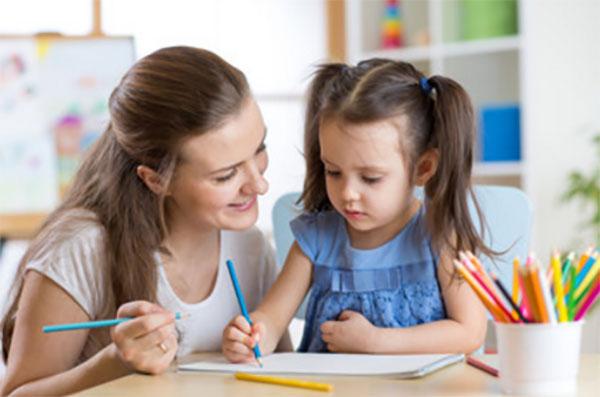 Девочка сидит возле мамы и рисует
