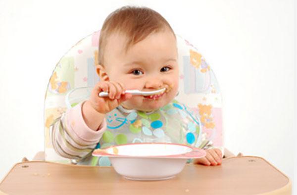 Маленький ребенок сам кушает с ложечки