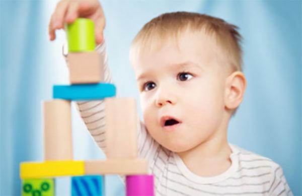 Двухлетний мальчик строит пирамиду из кубиков