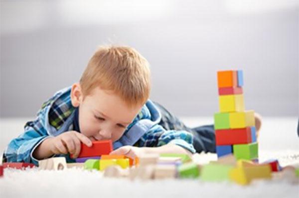 Мальчик играет разноцветными деревянными кубиками