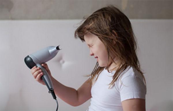 Девочка сушит волосы феном